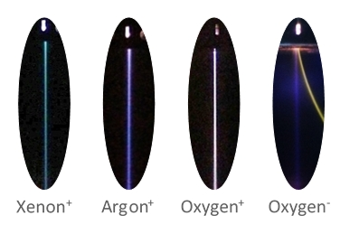 Photos of four different parallel beams: positive beams of xenon, argon, and oxygen, and a negative oxygen beam (including deflected electron beam)